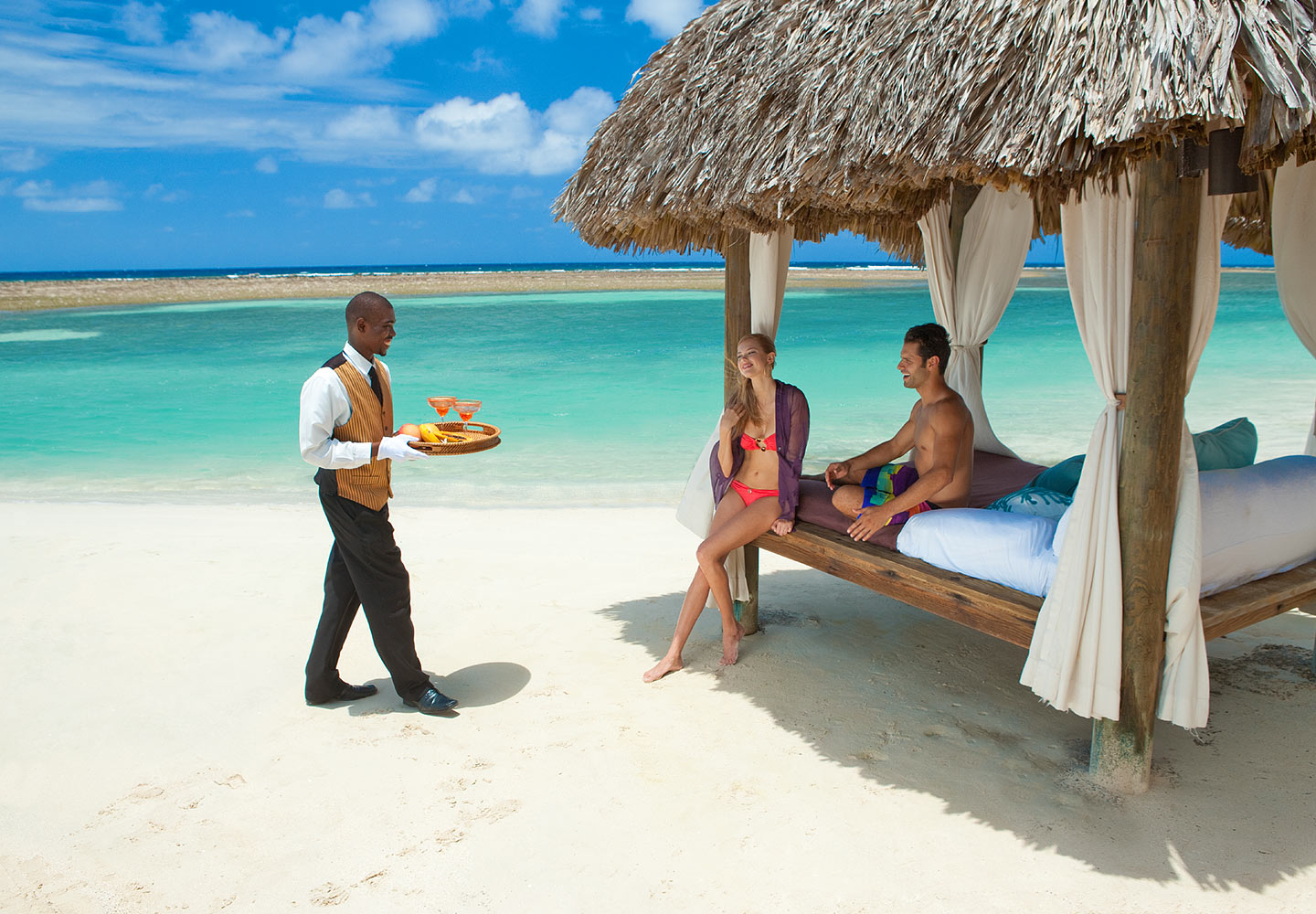 A valet delivering drinks to a cabana at Sandals Royal Caribbean, Jamaica